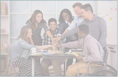 Photo of diverse coworkers around table with hands piled including African-American man in wheelchair